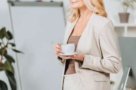 Photo for Cropped shot of smiling businesswoman holding cup of coffee in office - Royalty Free Image