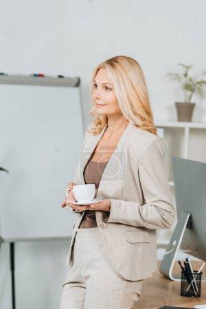Photo pour Belle femme souriante tenant la tasse de café et à la recherche de suite au bureau - image libre de droit