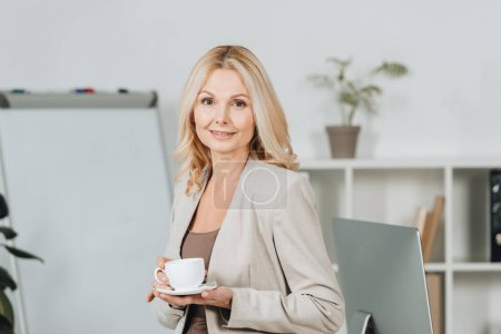 Photo for Beautiful businesswoman holding cup of coffee and smiling at camera in office - Royalty Free Image