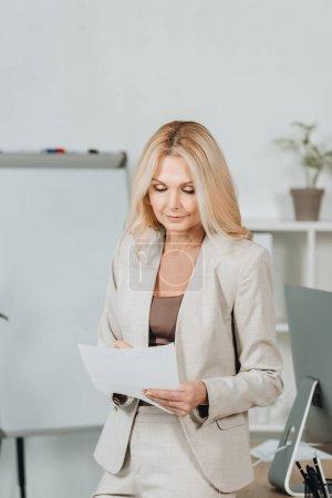 Foto de Centrada a madura empresaria sosteniendo papel y tomar notas en la oficina - Imagen libre de derechos