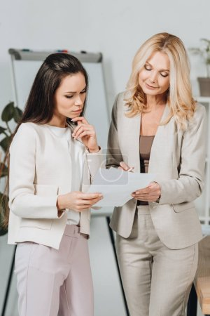 smiling mature businesswoman pointing at papers and discussing work with young female colleague in office