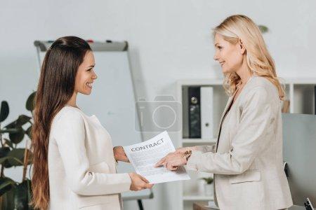 Photo pour Vue latérale des femmes d'affaires gaies détenant un contrat et se souriant mutuellement dans le bureau - image libre de droit