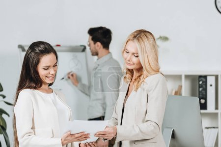 beautiful smiling businesswomen holding papers and young businessman writing on whiteboard behind in office