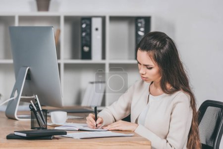 concentrated young businesswoman sitting at workplace and writing in notebook