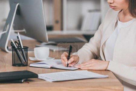 Photo pour Recadrée coup de jeune femme d'affaires assis au milieu de travail et écrire dans cahier - image libre de droit