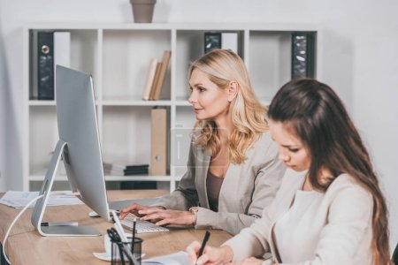Photo for Young businesswoman taking notes and mature female colleague using desktop computer at workplace - Royalty Free Image