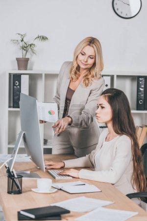 Photo pour Jeune femme d'affaires à l'aide d'ordinateur de bureau et mentor de femelle mature pointant sur écran - image libre de droit