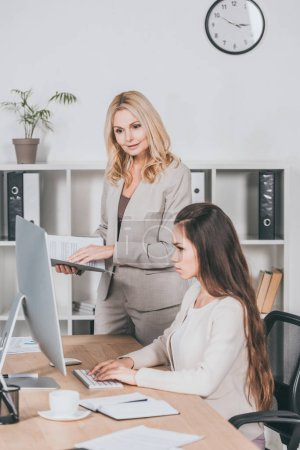 mature business mentor with folder and young businesswoman looking at desktop computer in office