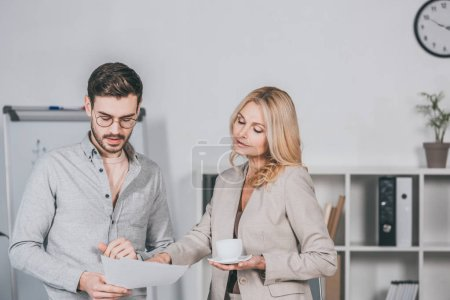 Photo pour Mentor femme d'affaires tenant une tasse de café et regardant jeune homme d'affaires tenant des papiers en fonction - image libre de droit