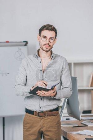 Photo pour Sérieux jeune entrepreneur en lunettes tenant le bloc-notes et en regardant la caméra dans le bureau - image libre de droit