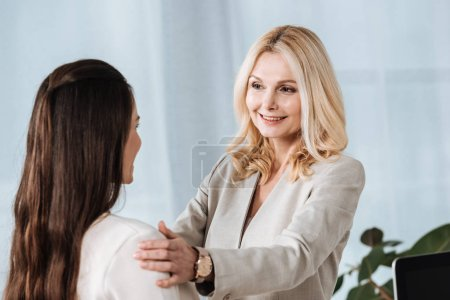 beautiful smiling female business mentor looking at young female colleague in office