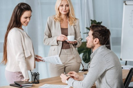 mature businesswoman holding cup of coffee and looking at young colleagues working with contract in office