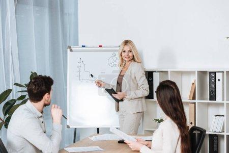 souriante femme d'affaires mature pointant du doigt le tableau blanc et regardant les jeunes collègues au bureau