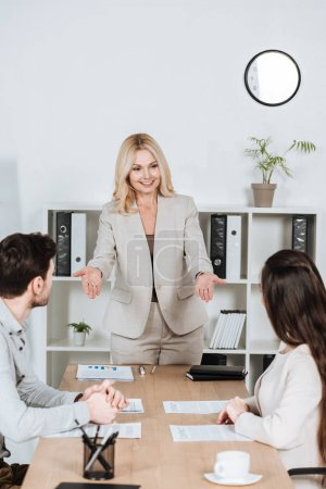 smiling female business mentor looking at young colleagues sitting at workplace