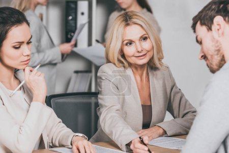 smiling mature businesswoman pointing at papers and working with young colleagues in office