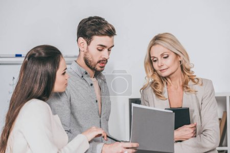 focused professional business colleagues discussing documents in office