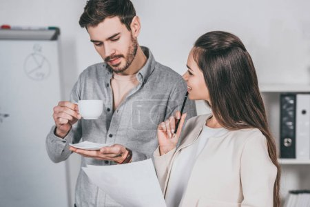 business mentor holding cup of coffee and discussing papers with female colleague in office