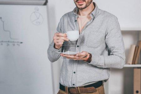 Photo pour Recadrée tir du jeune homme d'affaires barbu tenant la tasse de café et soucoupe en bureau - image libre de droit