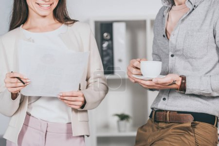 cropped shot of smiling business colleagues holding cup of coffee and papers in office