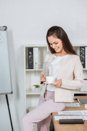 smiling young businesswoman sitting on desk and looking at cup of coffee in office