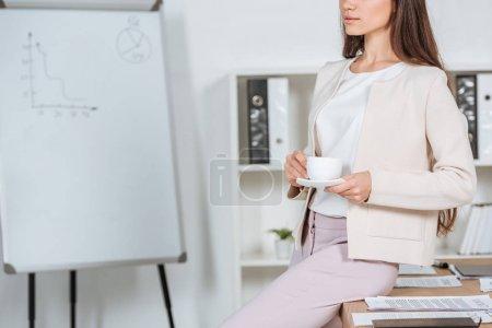 Photo pour Plan recadré de jeune femme d'affaires assise sur la table et tenant une tasse de café sur le lieu de travail - image libre de droit