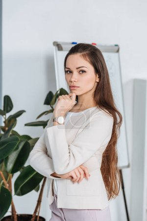 serious professional young businesswoman standing with hand on chin and looking at camera in office