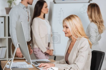 Photo for Side view of smiling businesswoman using desktop computer and young colleagues working with whiteboard behind - Royalty Free Image