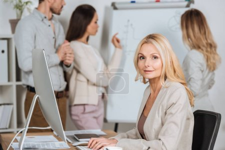 mature businesswoman using desktop computer and looking at camera while young colleagues working with whiteboard behind