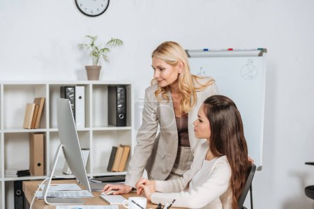 young businesswoman sitting at desk and looking at smiling female mentor using desktop computer in office