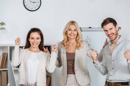 cheerful professional business colleagues shaking fists and smiling at camera in office