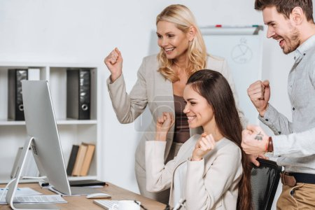 happy business mentor with smiling young colleagues shaking fists and looking at desktop computer in office