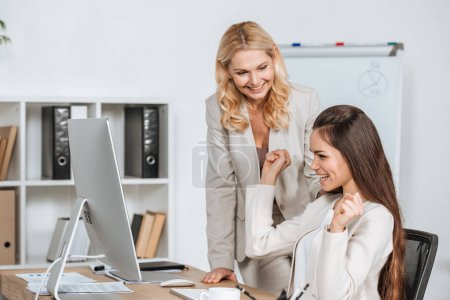 Photo for Smiling mature businesswoman looking at cheerful young colleague using desktop computer at workplace - Royalty Free Image