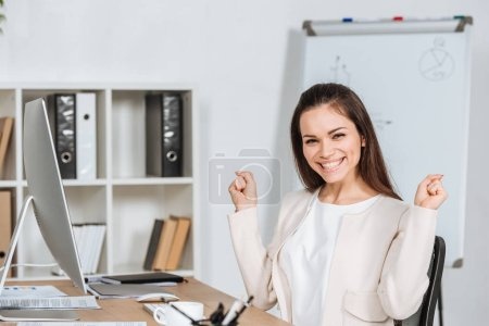 happy young businesswoman triumphing and smiling at camera in office