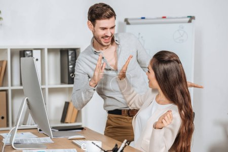 Photo for Happy young businesspeople giving high five and smiling each other at workplace - Royalty Free Image