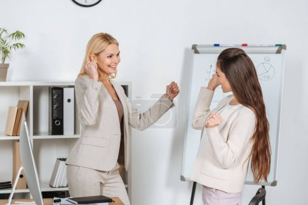 cheerful businesswomen triumphing and smiling each other in office