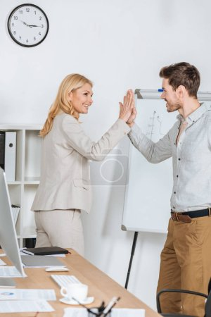 Photo for Happy businessman and businesswoman smiling and giving high five in office - Royalty Free Image