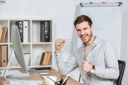 Photo for Happy young businessman triumphing and smiling at camera in office - Royalty Free Image