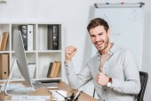 happy young businessman triumphing and smiling at camera in office
