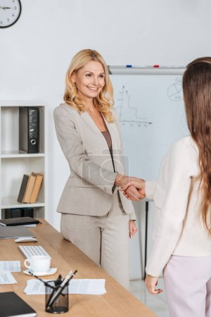 cropped shot of young and mature businesswomen shaking hands in office