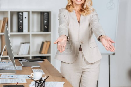 Photo for Cropped shot of smiling businesswoman greeting someone and gesturing with hands in office - Royalty Free Image