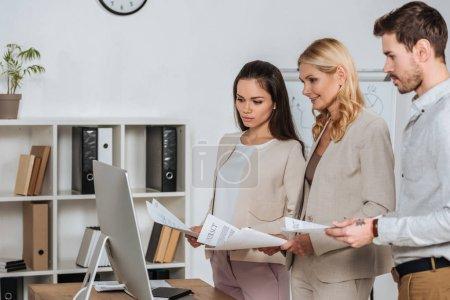 fokussierte Geschäftsleute, die Papiere halten und Desktop-Computer im Büro benutzen