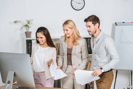 Photo for Smiling professional businesspeople holding papers and looking at desktop computer in office - Royalty Free Image