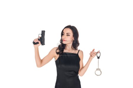 attractive elegant secret agent in black dress holding gun and handcuffs, isolated on white