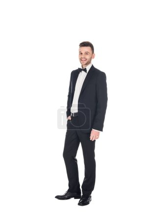 handsome smiling man posing in black tuxedo and tie bow isolated on white