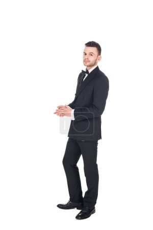 handsome young man posing in black tuxedo and tie bow isolated on white