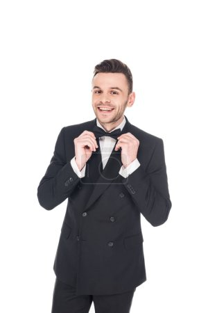 Photo for Cheerful elegant man posing in black tuxedo and tie bow isolated on white - Royalty Free Image
