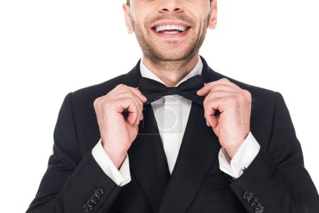 cropped view of smiling man posing in black tuxedo and tie bow isolated on white