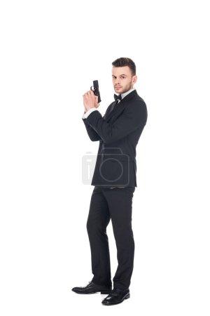elegant secret agent in black suit holding gun, isolated on white