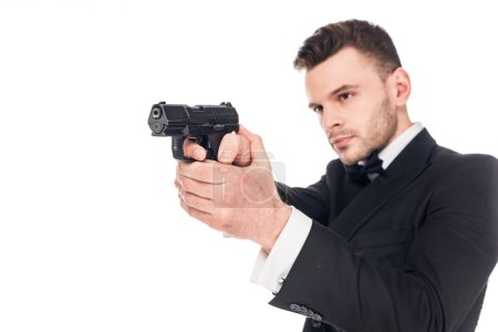 handsome serious killer in black suit aiming with handgun, isolated on white