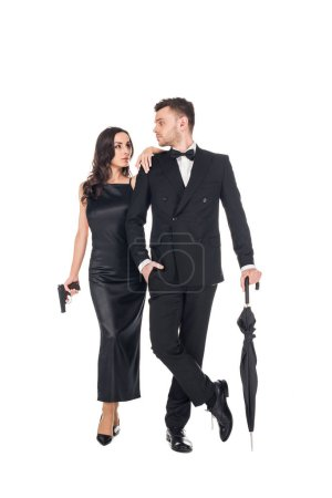 young elegant couple of killers in black clothes posing with gun and umbrella, isolated on white